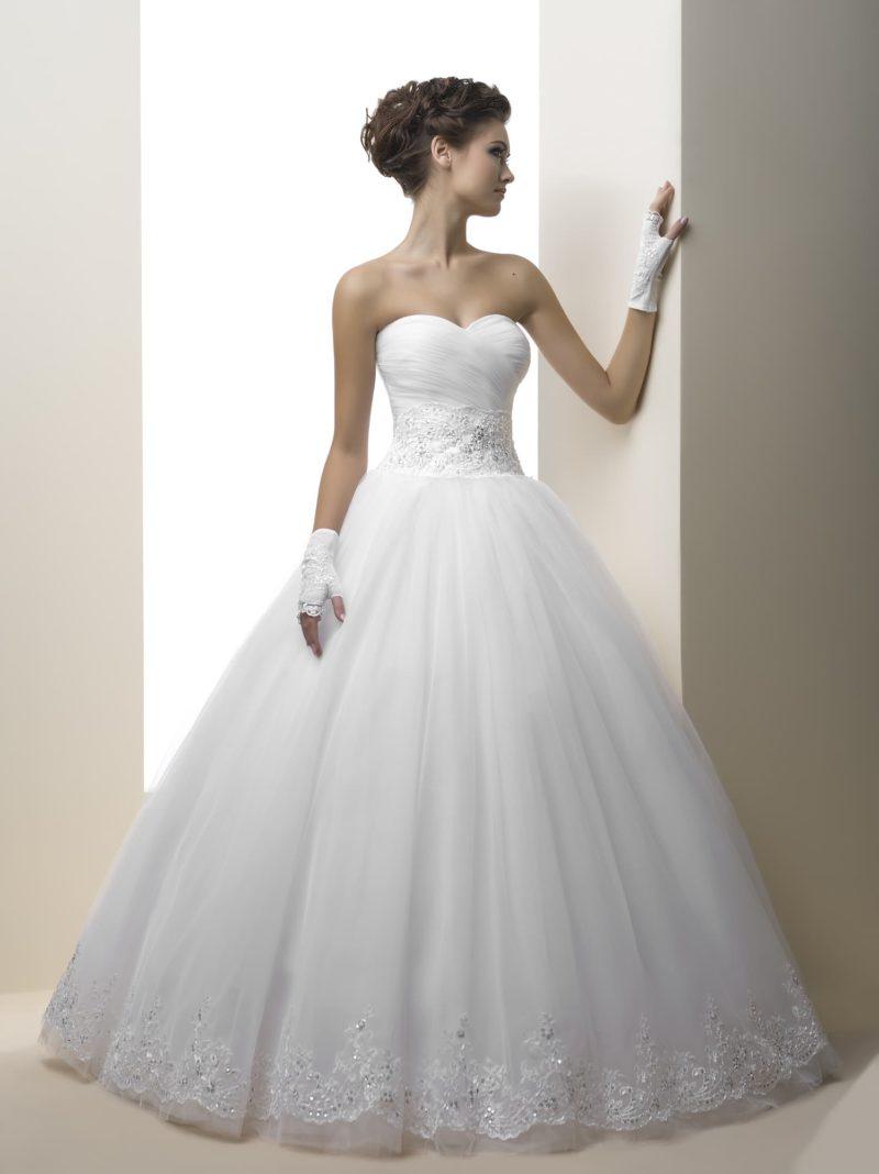 Открытое свадебное платье с кружевным декором по низу подола и драпировками на корсете.