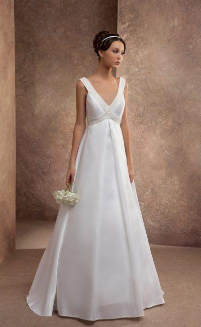 Свадебное платье А-силуэта с широкими бретелями, украшенными бисером, и завышенной талией.