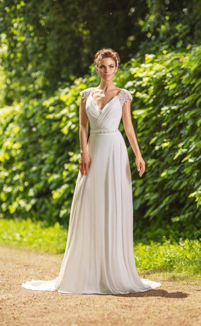 Утонченное свадебное платье с глубоким декольте и изящными короткими рукавами.