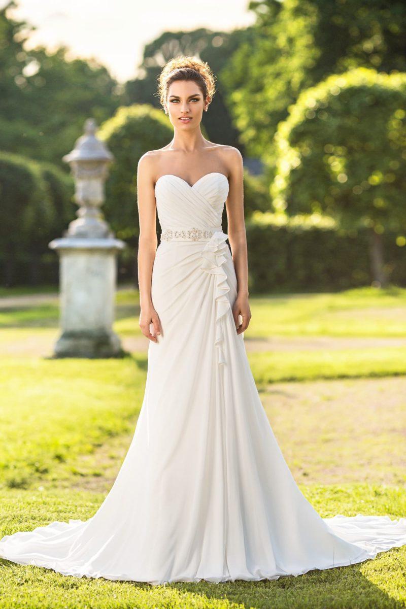 Изящное свадебное платье, облегающее фигуру легкими оборками ткани и открывающее декольте.