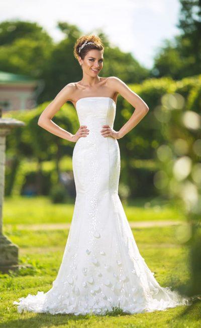 Свадебное платье облегающего кроя с объемным декором нижней части подола и лифом прямого кроя.