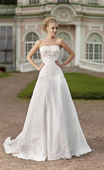 Фактурное свадебное платье с открытым лифом прямого кроя и многослойной юбкой.