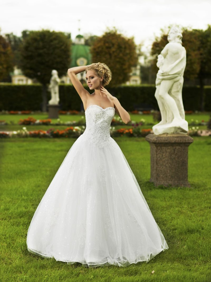 Традиционное свадебное платье пышного кроя с фактурным открытым корсетом и длинным шлейфом.