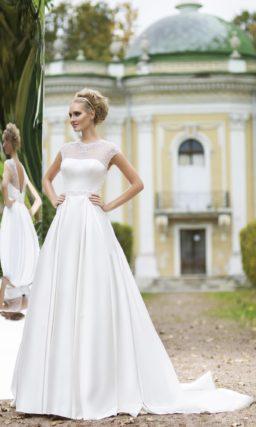 Утонченное свадебное платье из атласа с полупрозрачной вставкой над декольте и длинным шлейфом.