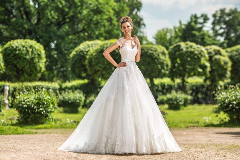 Торжественное свадебное платье с прозрачной вставкой на лифом и плотным кружевным декором.