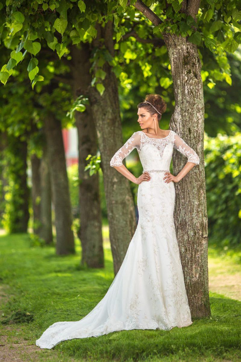 Прямое свадебное платье с округлым вырезом и длинными кружевными рукавами,  а также узким поясом.