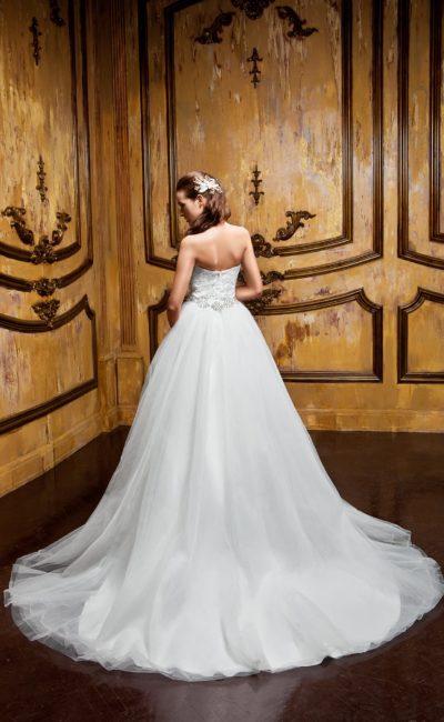 Роскошное свадебное платье с длинным многослойным шлейфом и открытым корсетом.