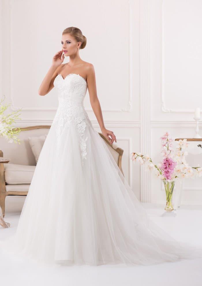 Классическое свадебное платье с многослойным подолом и открытым корсетом, покрытым кружевом.
