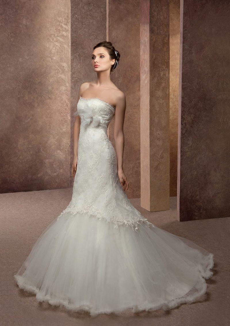 Открытое свадебное платье силуэта «русалка» с кружевной отделкой и многослойным подолом.
