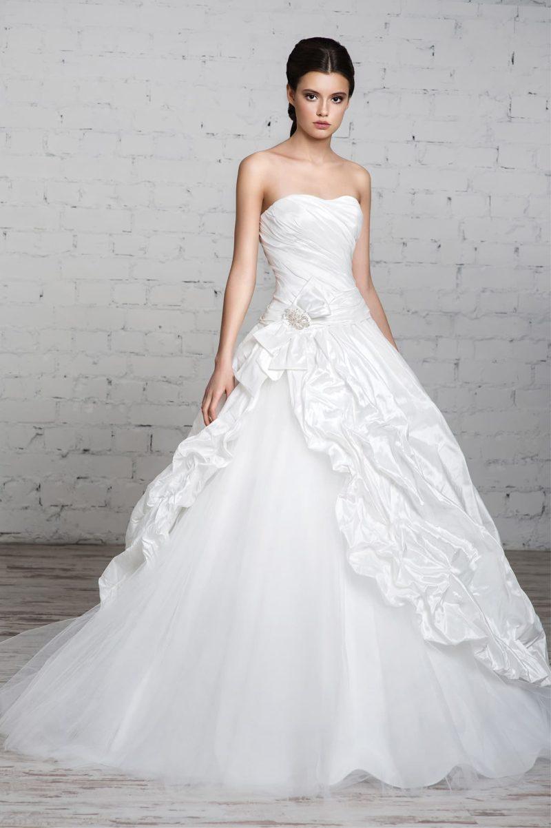 Открытое свадебное платье пышного кроя с оборками из плотной ткани по роскошному подолу.