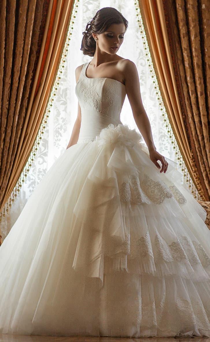 Свадебное платье с кокетливой пышной юбкой, украшенной сбоку оборками с кружевным декором.