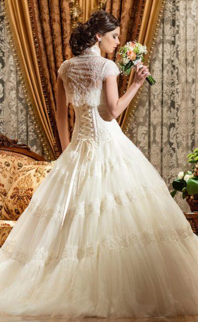 Открытое свадебное платье с кружевным болеро и пышной юбкой, декорированной аппликациями.