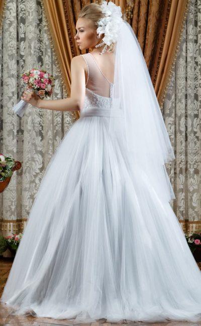 Свадебное платье пышного кроя с широким поясом и полупрозрачной вставкой над корсетом.
