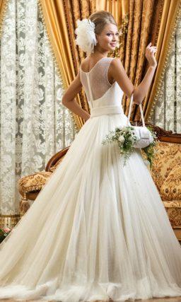 Свадебное платье со вставкой над лифом, изящным поясом на талии и пышной юбкой.