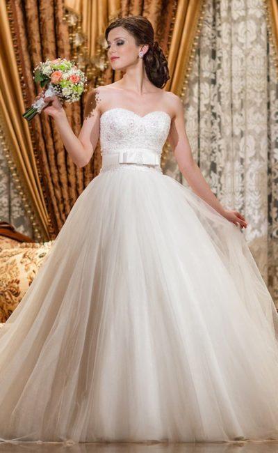 Свадебное платье с открытым лифом, украшенным бисером, и атласным поясом с бантом.