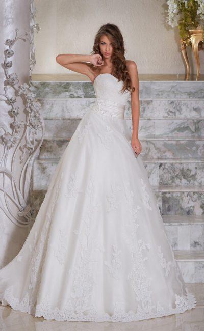 Свадебное платье с крупными кружевными аппликациями и широким атласным поясом на талии.