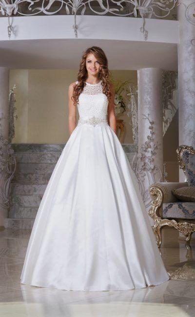Пышное свадебное платье с узким сияющим поясом и закрытым ажурной тканью лифом.