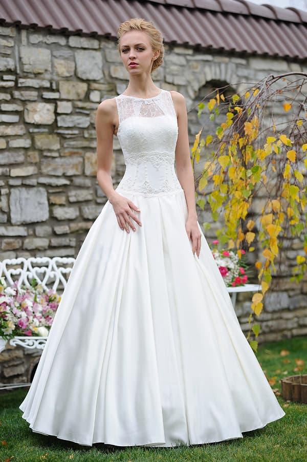 Изысканное свадебное платье с вырезом под горло и заниженной линией талии.