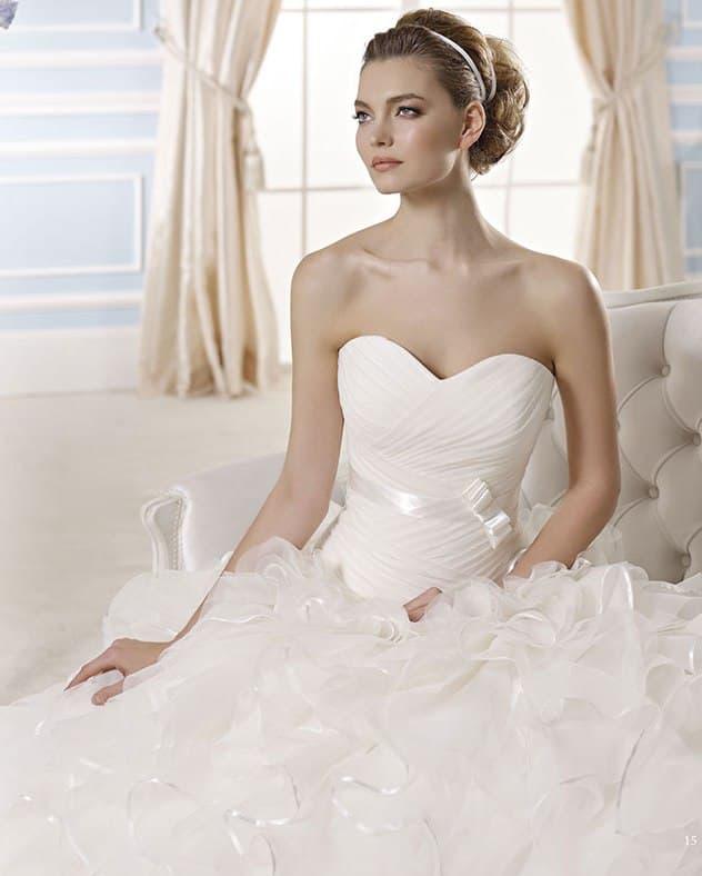 Свадебное платье с изящным вырезом и пышной юбкой под слоем объемных оборок.