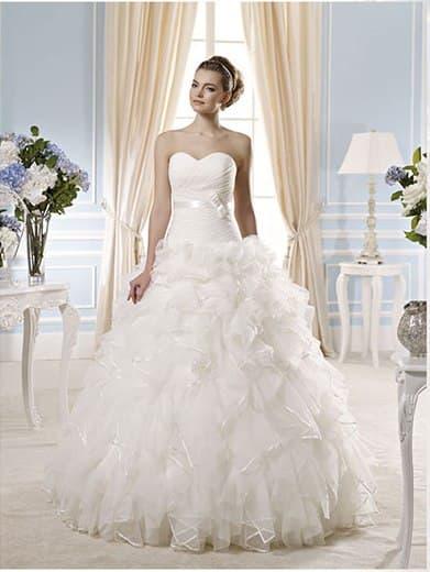 Незабываемое свадебное платье с множеством оборок на юбке и классическим верхом.