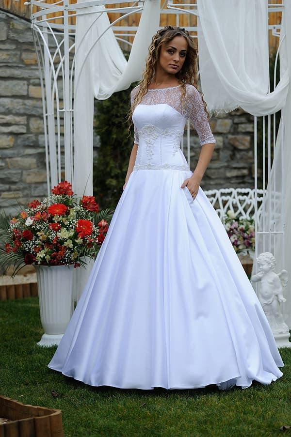 Сияющее свадебное платье торжественного кроя с кружевом над вырезом.