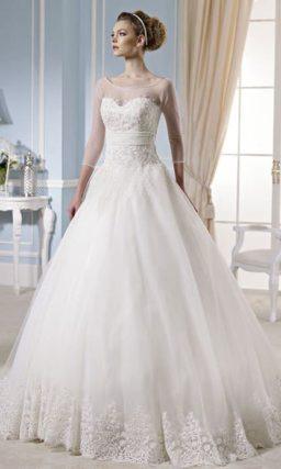 Свадебное платье с длинным полупрозрачным рукавом и объемной юбкой.
