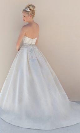 Свадебное платье молочного цвета со стразами, украшающими корсет.