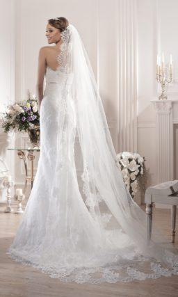 Облегающее свадебное платье с кружевной отделкой и узким поясом из атласа под лифом.