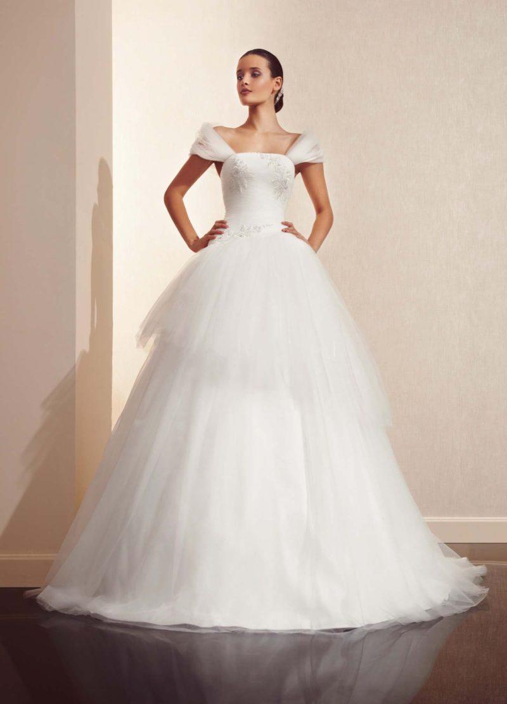 Оригинальное свадебное платье пышного кроя с объемной баской и широкими полупрозрачными бретелями.
