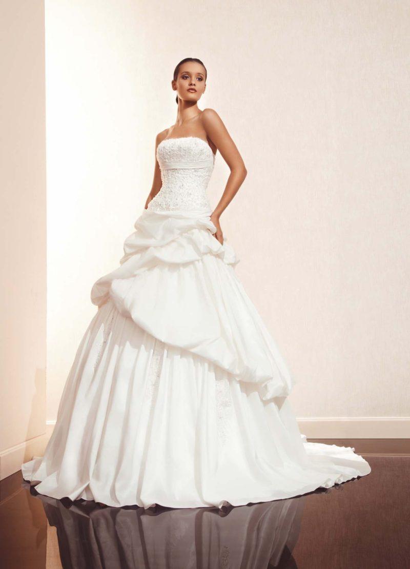 Соблазнительное свадебное платье с лифом прямого кроя и пышными оборками по подолу.