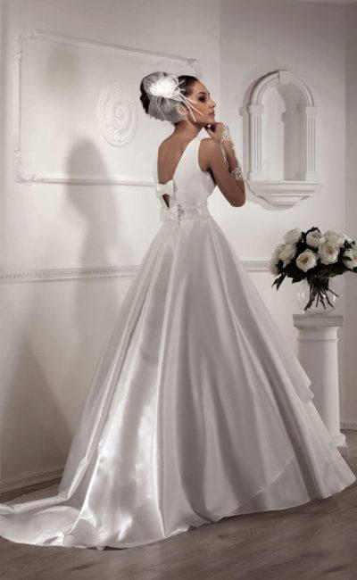 Глянцевое свадебное платье пышного кроя с открытой спинкой, украшенной бантами.
