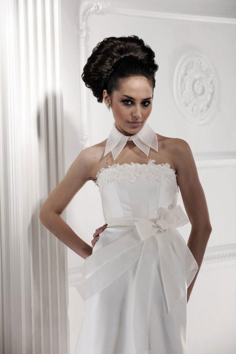 Прямое свадебное платье с широким поясом с бантом и объемным декором лифа.