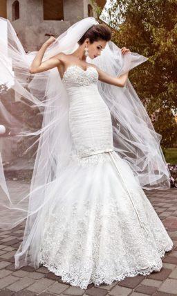 Свадебное платье «рыбка» с кружевной отделкой и необычным поясом на подоле.