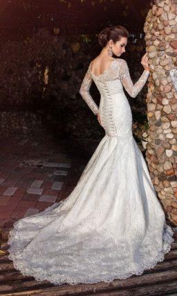 Свадебное платье «русалка» с впечатляющим шлейфом и длинными рукавами.