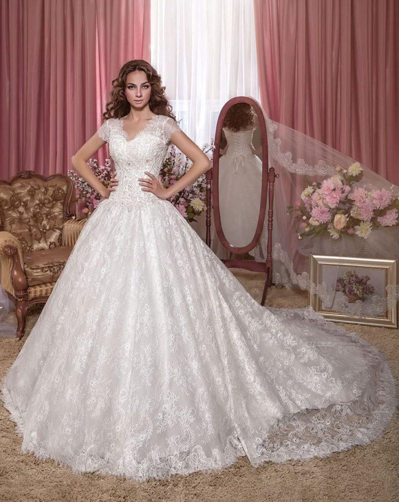 Потрясающее свадебное платье с пышной кружевной юбкой и небольшим вырезом.