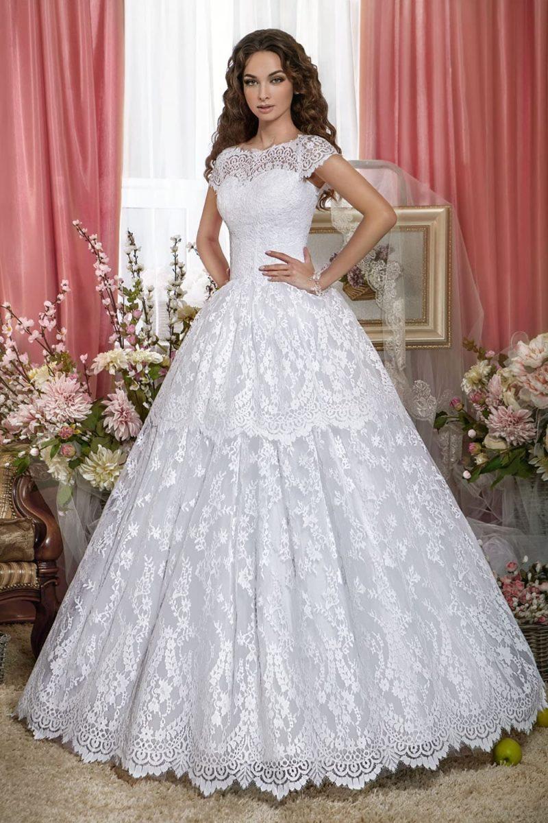 Свадебное платье с коротким рукавом и выразительным кружевом на пышной юбке.