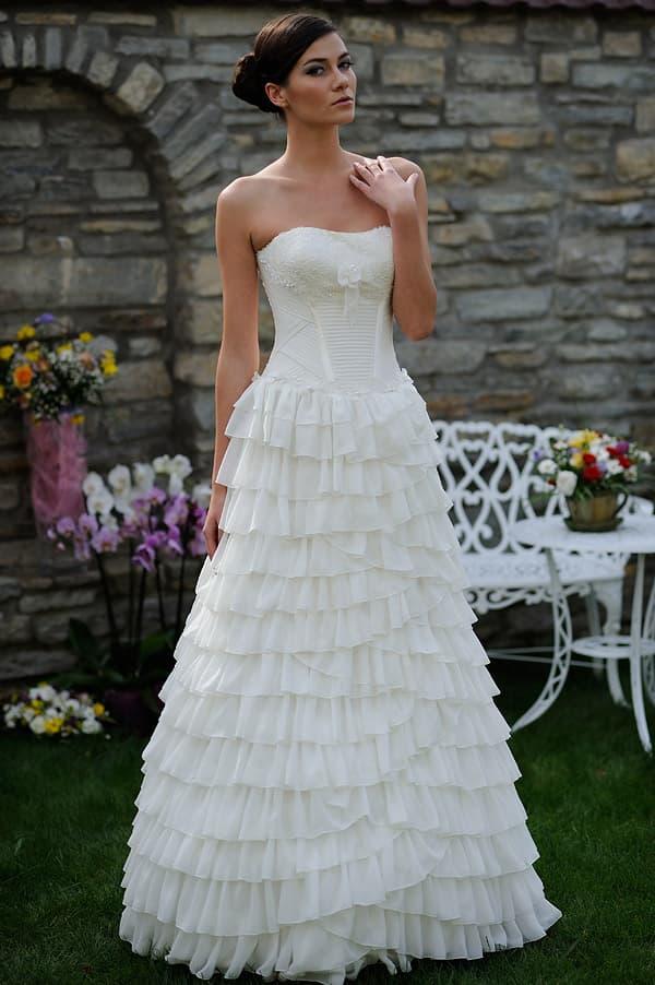 Свадебное платье с кружевным лифом и юбкой А-кроя, покрытой оборками.