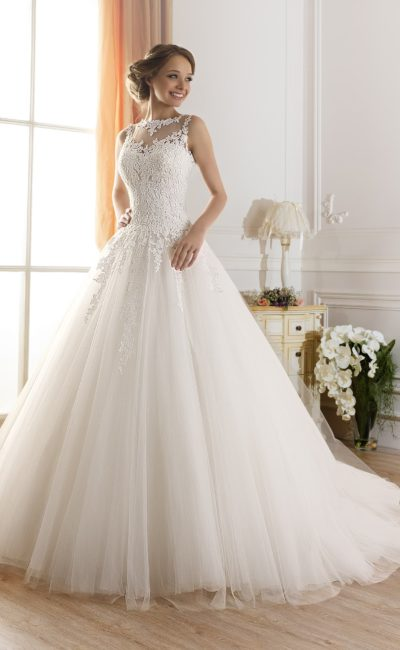 Свадебное платье с закрытым лифом, покрытым плотными кружевными аппликациями, и пышной юбкой.