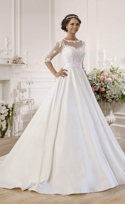 Деликатное свадебное платье с полупрозрачной вставкой над лифом и атласной юбкой.