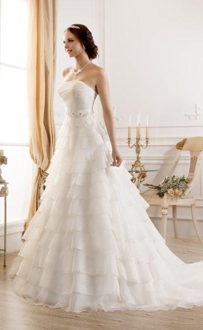 Пышное свадебное платье с открытым корсетом и стильной юбкой, покрытой множеством оборок.