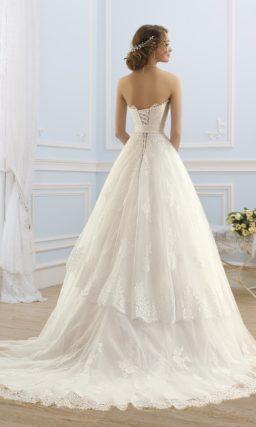 Свадебное платье с открытым кружевным корсетом и пышной многоярусной юбкой со шлейфом.