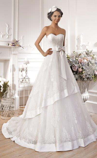 Свадебное платье с открытым лифом в форме сердца, поясом, украшенным бантом, и многослойной юбкой.