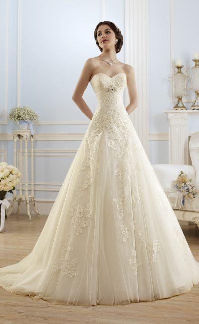 Свадебное платье цвета слоновой кости, декорированное кружевными аппликациями.
