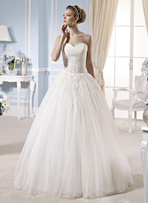 Пышное свадебное платье в классическом стиле, украшенное кружевной тканью.