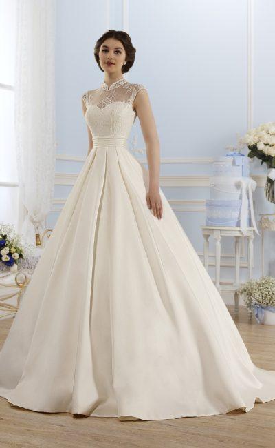 Атласное свадебное платье с закрытым верхом из кружева и пышной юбкой со шлейфом.