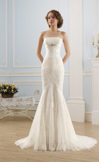 Облегающее свадебное платье с открытым лифом прямого кроя и изящным кружевным декором.