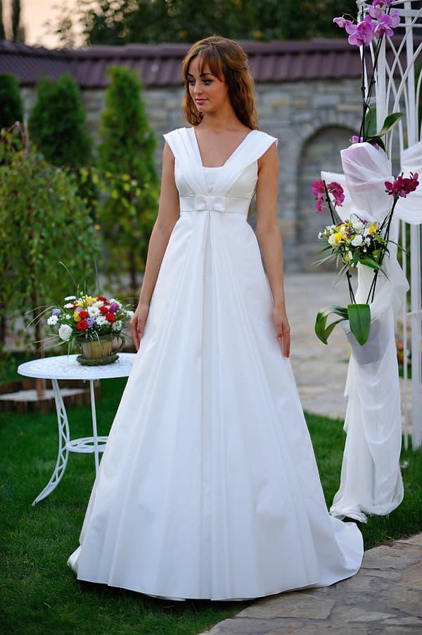 Свадебное платье А-силуэта с завышенной талией, широкими бретелями и шлейфом.