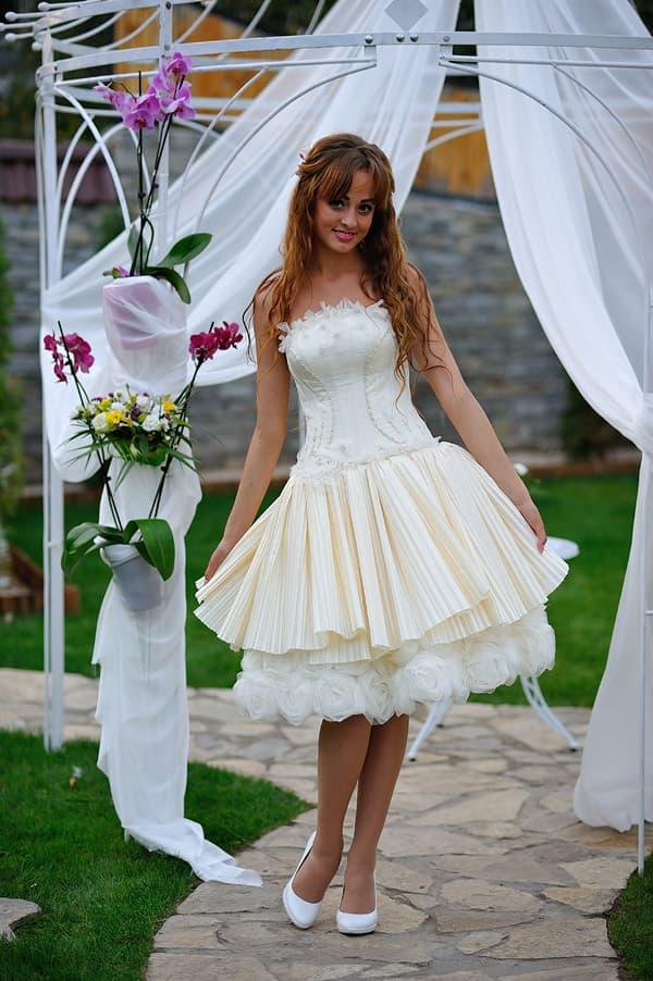 Короткое свадебное платье из плотной ткани, с объемным декором на лифе.