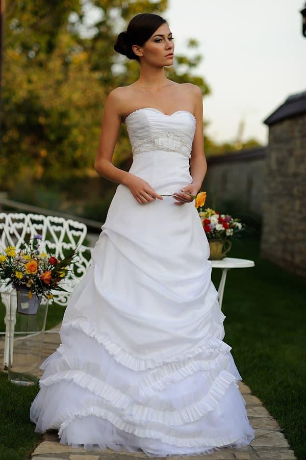 Романтичное свадебное платье «принцесса» с волнами ткани по подолу.