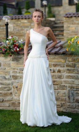 Эффектное свадебное платье с асимметричным верхом и оборками на подоле.